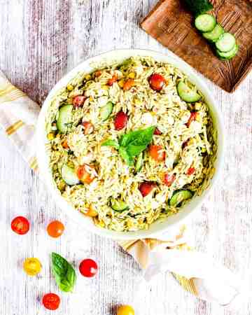 Serving bowl of pesto orzo salad with cherry tomatoes and sliced cucumber.