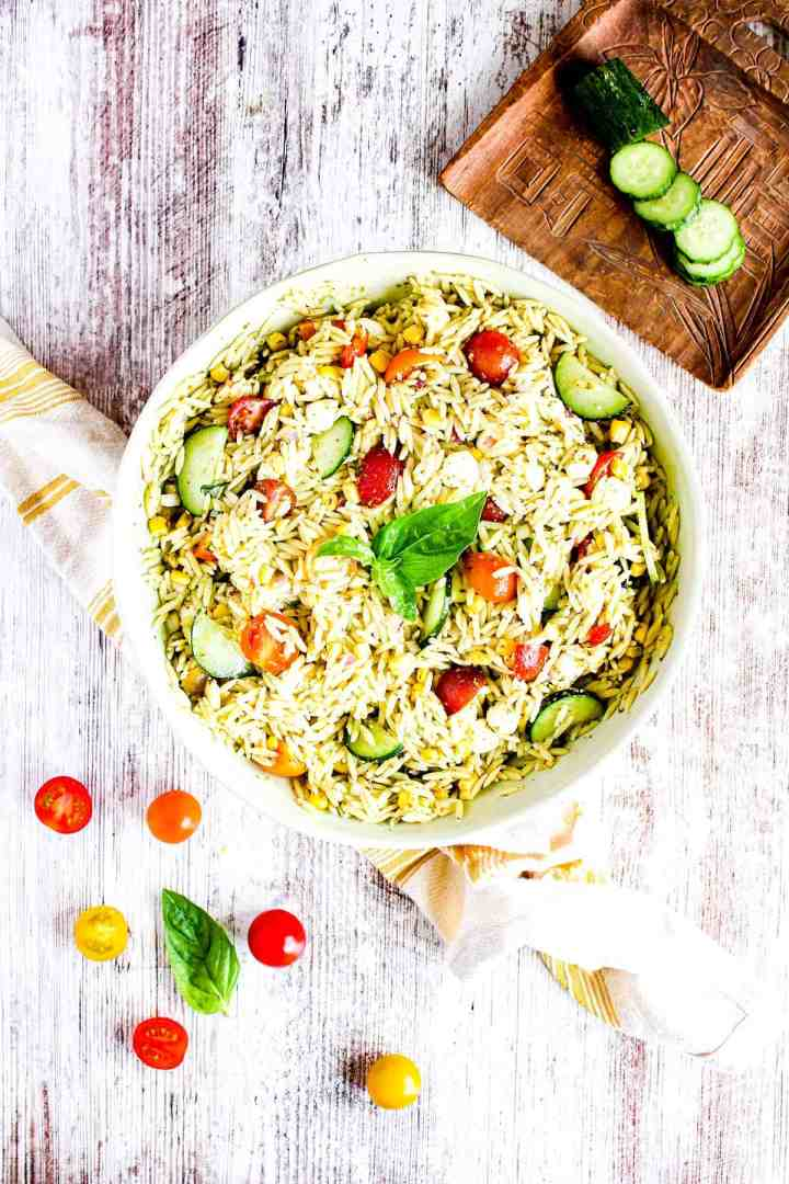 Serving bowl of orzo pesto salad with summer vegetables, a towel, tomatoes, and sliced cucumber.