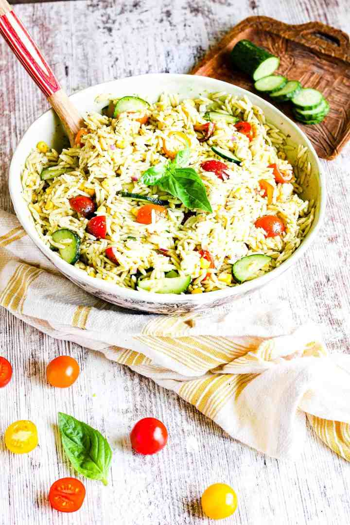 Bowl of orzo pesto salad with a spoon.