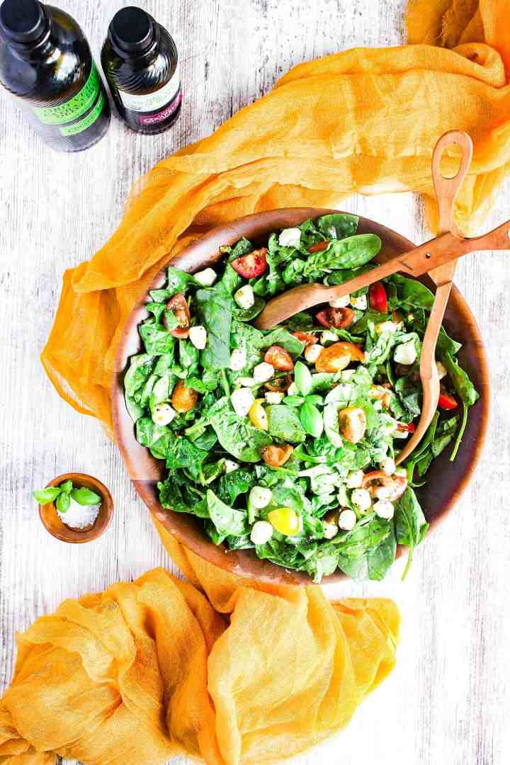 Bowl of salad with a small bowl of salt and bottles of olive oil and vinegar.