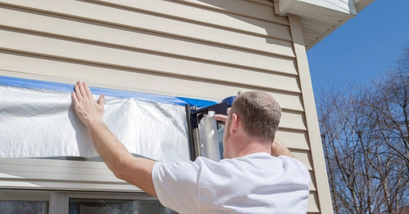 applying tape to house siding