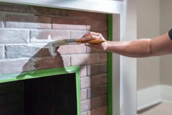 Man painting on brick fireplace where FrogTape multi-surface is used.