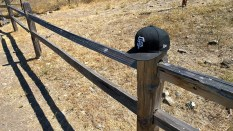 Baseball cap sitting on a fence post.