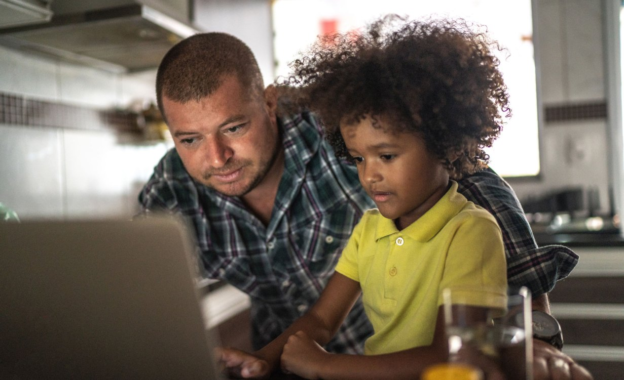 Father helps child with homework on laptop