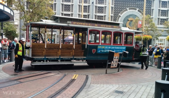 A cable car is being turn at the end of Powell St in order to change direction.