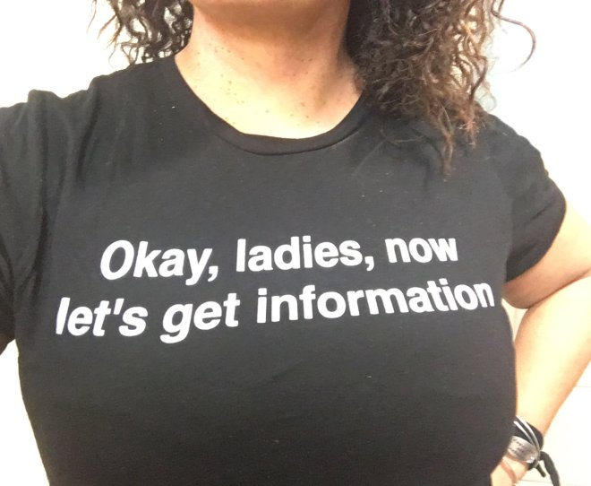 "black t-shirt that says ""Okay, ladies, now get's get information"""