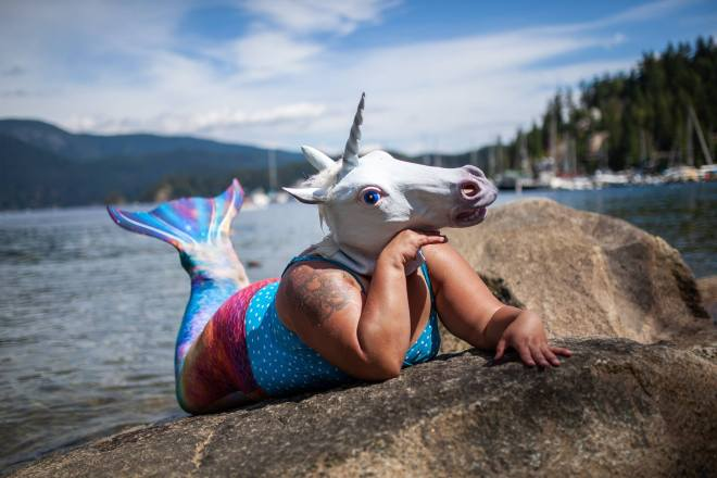 photo of me in a turquoise polka dot bathing suit, with a rainbow mermaid tail, and a unicorn mask on, posing on a rock with a water and blue sky in the background