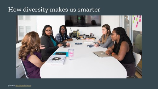 5 women of colour sitting in a meeting room, talking across a table
