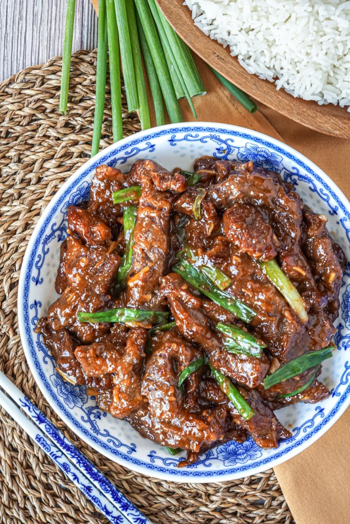 Aerial view of Mongolian Beef in a white and blue bowl next to a wooden bowl of steamed rice and a bunch of green onions.