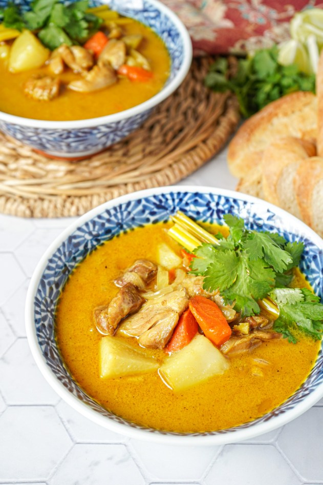 Close up of Cà Ri Gà (Vietnamese Chicken Curry) in two bowls next to baguette slices.