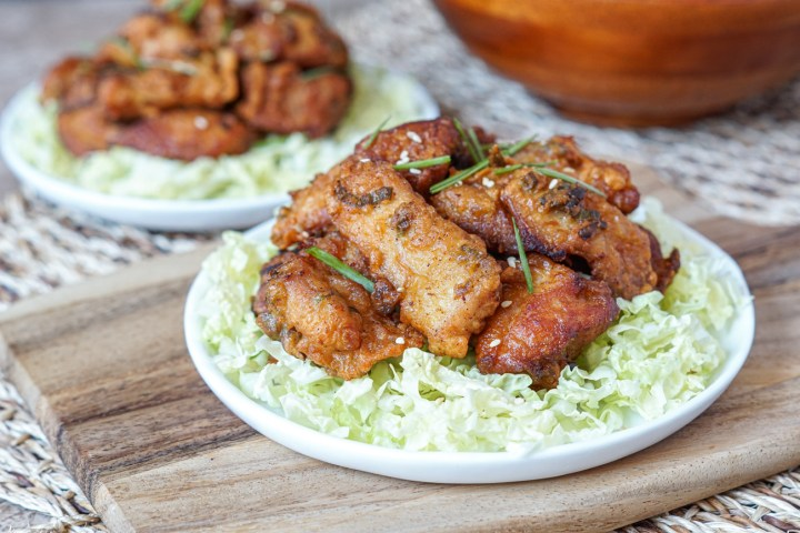 Mochiko Chicken (Hawaiian Fried Chicken) on two white plates over shredded cabbage.