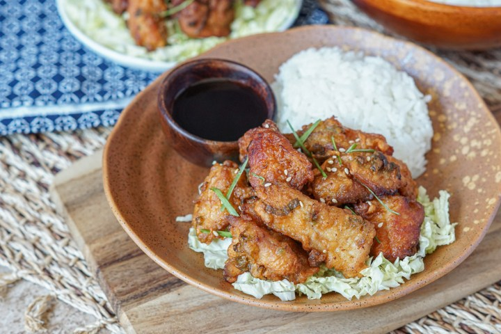 Mochiko Chicken (Hawaiian Fried Chicken) on a brown plate with white rice, shredded cabbage, and soy sauce.