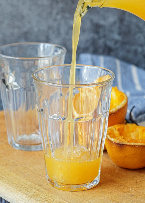 Pouring Roasted Vanilla Orange Juice into a tall, clear glass.