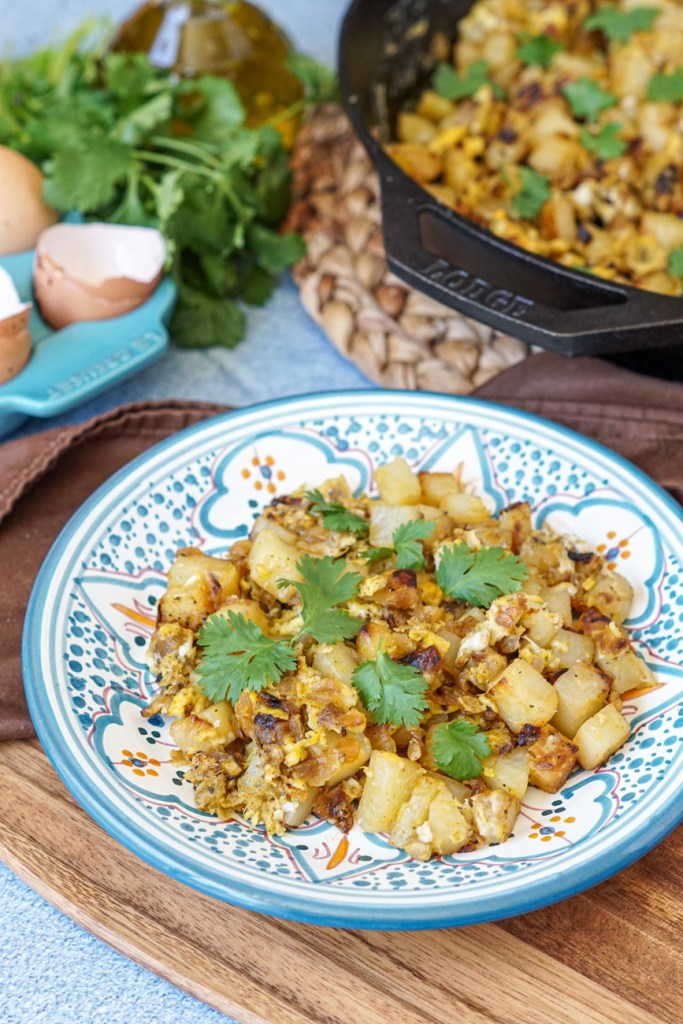 Batata Wa Bayd (Lebanese Potatoes and Eggs) on a blue and white plate with egg shells, cilantro, olive oil, and a cast iron skillet in the background.