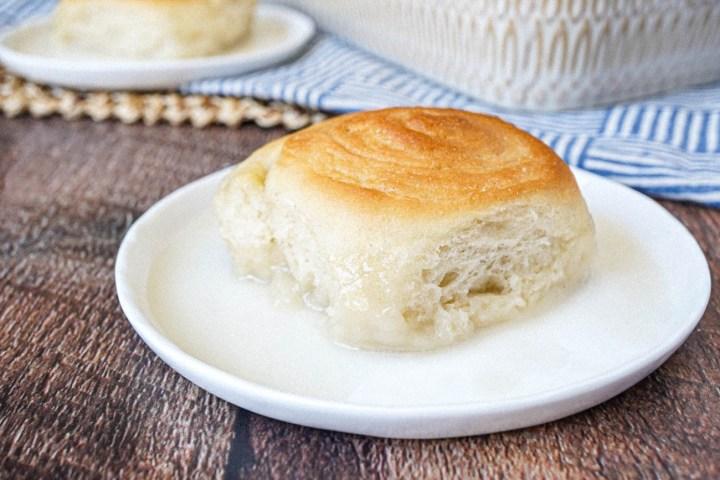 Pani Popo (Samoan Sweet Coconut Bun) on two white plates with coconut sauce.