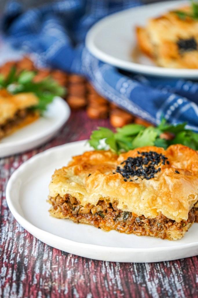 Close up of Kıymalı Tepsi Böreği (Turkish Phyllo Pastry with Beef) on a white plate.