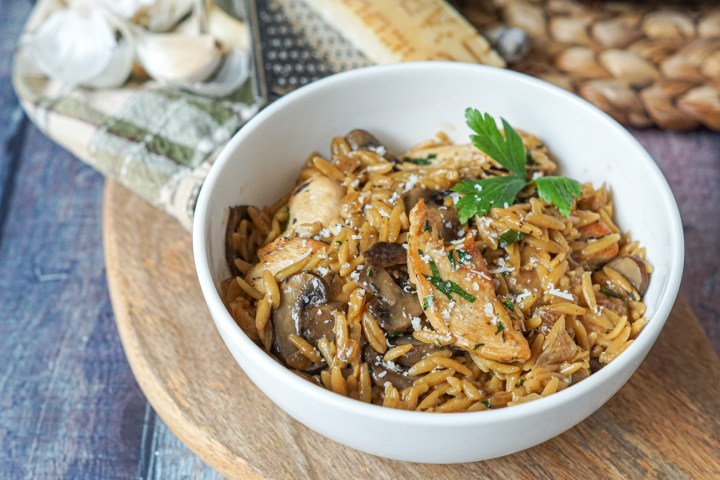 Chicken and Mushroom Orzo in a white bowl on a wooden platter next to garlic cloves and a Parmesan rind.