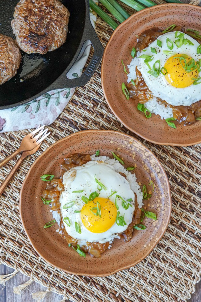 Aerial view of two brown plates of Loco Moco (Hawaiian Beef and Egg over Rice) topped with a fried egg next to two copper spoons, green onions, and a cast iron skillet with two beef patties.