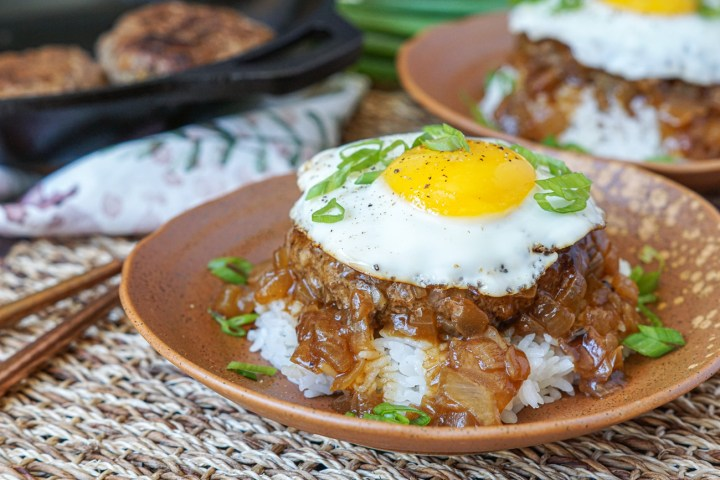 Two brown plates of Loco Moco with rice, beef patty, caramelized onion gravy, fried egg, and thinly sliced green onions.
