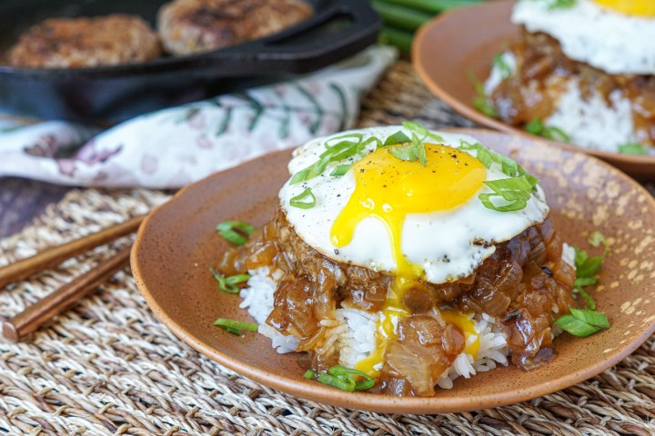 Two brown plates of Loco Moco (Hawaiian Beef and Egg over Rice) with a fried egg on top with a runny yolk.