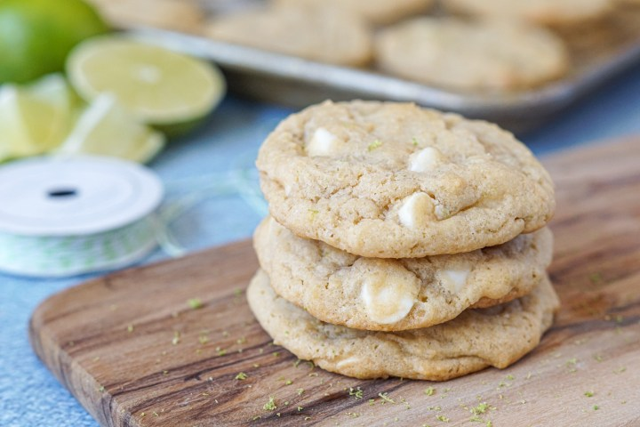 A stack of three White Chocolate Lime Cookies on a wooden board with lime slices in the background next to a silver baking sheet.