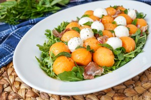 Cantaloupe Arugula Salad on a large white platter with fresh herbs in background.