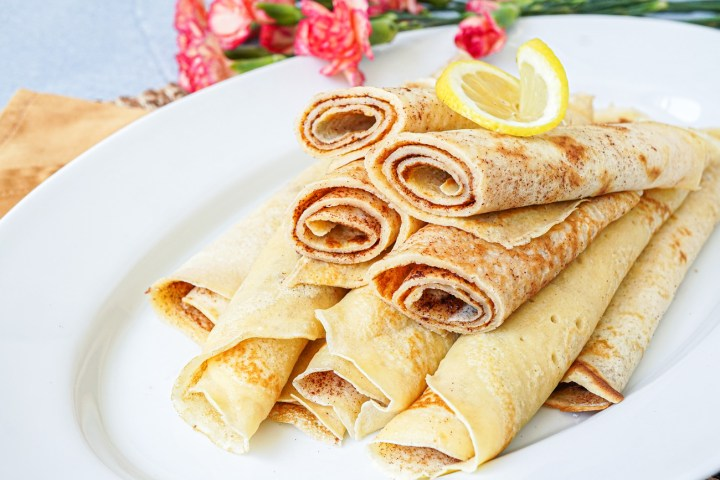 Close up of a stack of rolled Pannekoek on a white platter.