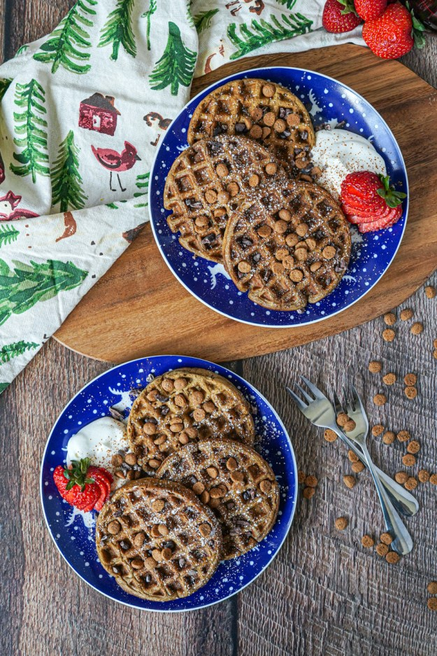 Aerial view of Gingerbread Waffles on two blue and white plates with whipped cream and strawberries.