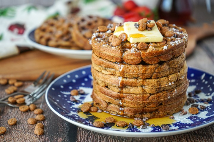 A stack of five Gingerbread Waffles on a blue and white plate and covered with butter, maple syrup, cacao nibs, and Schuddebuikjes.