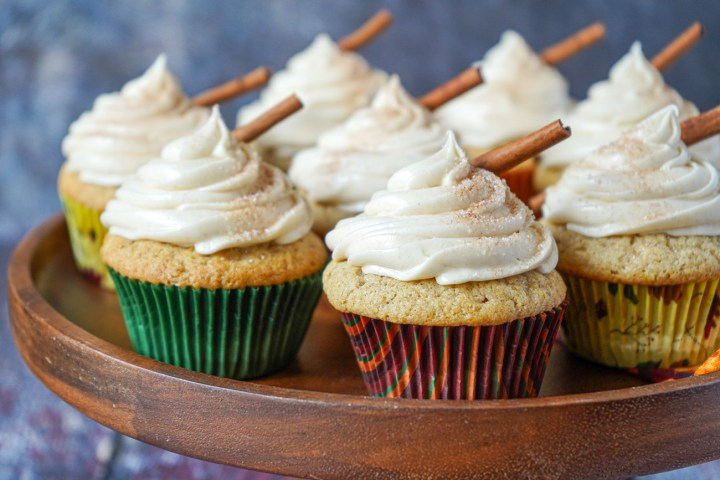 Eight Snickerdoodle Cupcakes on a wooden pedestal and topped with cinnamon sticks.