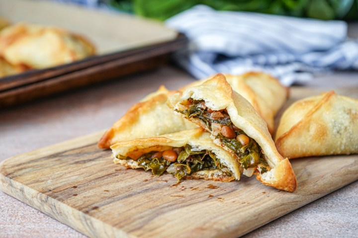 Fatayer bi Sabanekh (Lebanese Spinach Pies) on a wooden board with one cut in half.