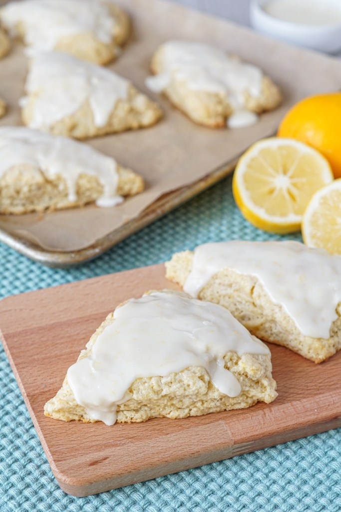Meyer Lemon Scones with a glaze on a wooden board and a baking sheet.
