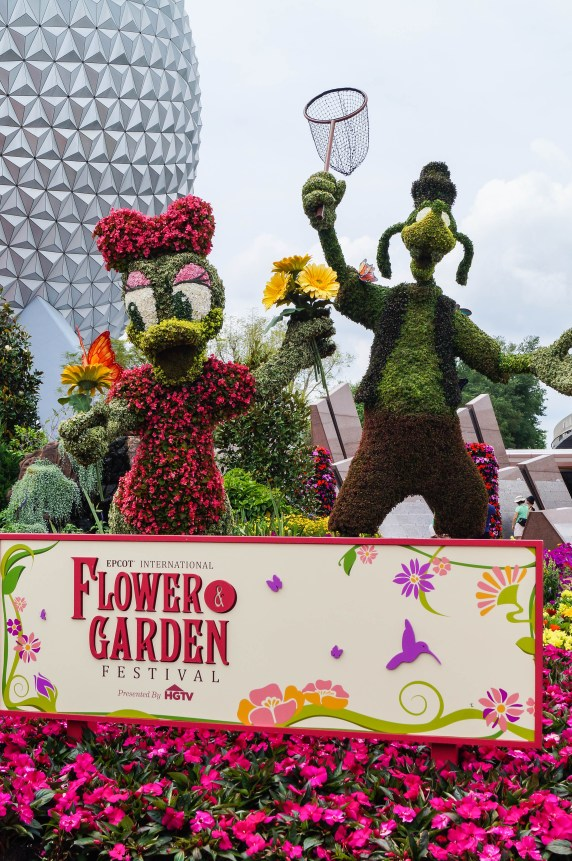 Epcot International Flower and Garden Festival sign with plants decorated as Daisy and Goofy.