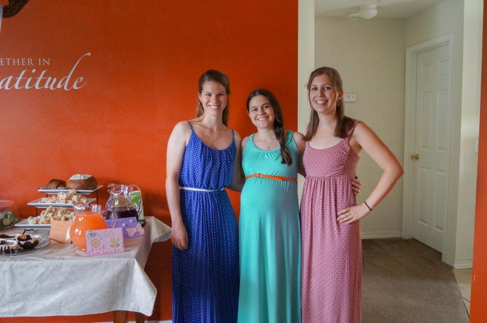 Three women standing together next to food table.