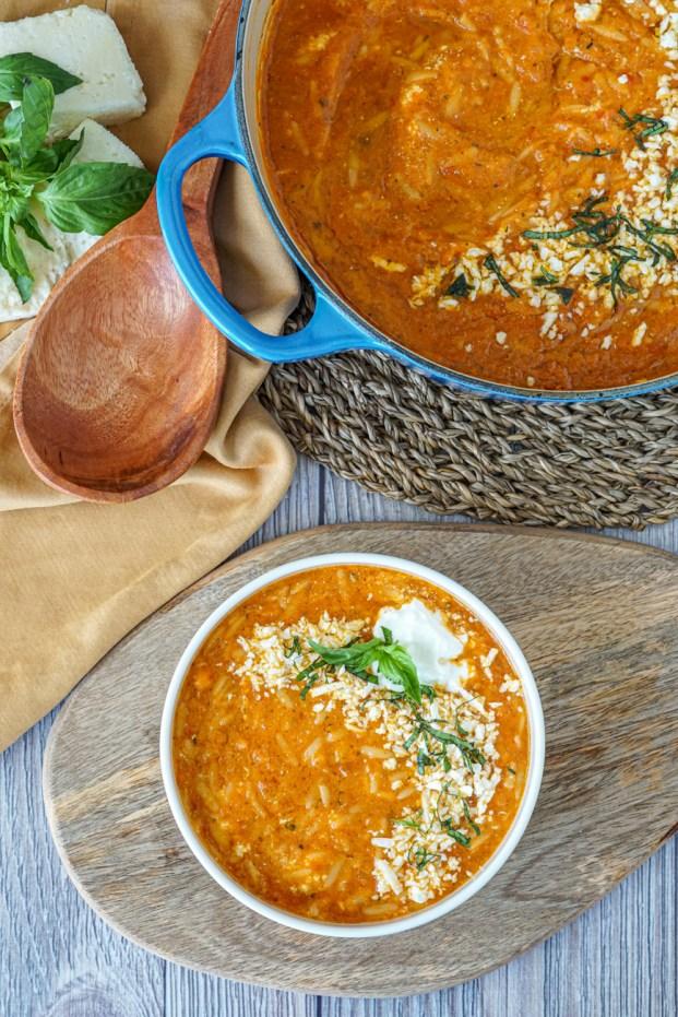 Domatosoupa Me Kritharaki (Greek Tomato Soup with Orzo) in a white bowl next to a blue pot, large wooden spoon, basil, and Kefalotyri cheese.