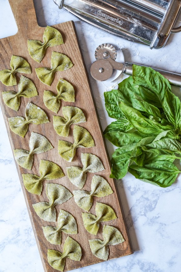 Aerial view of Homemade Basil Farfalle on a wooden board next to basil leaves and a pasta machine.