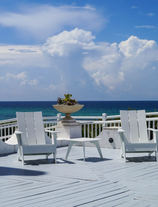 White wooden chairs on a white deck with the ocean in the background.