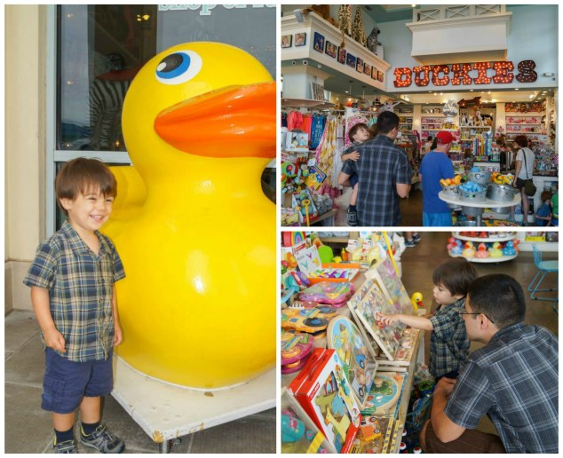 Standing next to a large yellow rubber duck and looking at puzzles inside Duckies.
