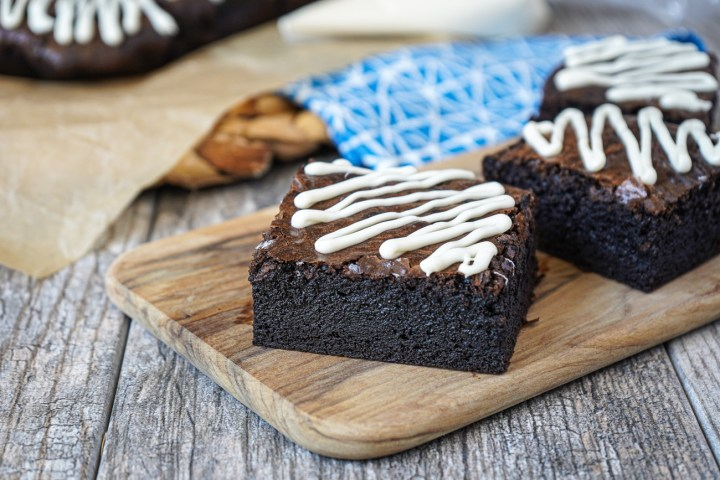 Three Dark Chocolate Brownies with a white chocolate drizzle on a wooden board.