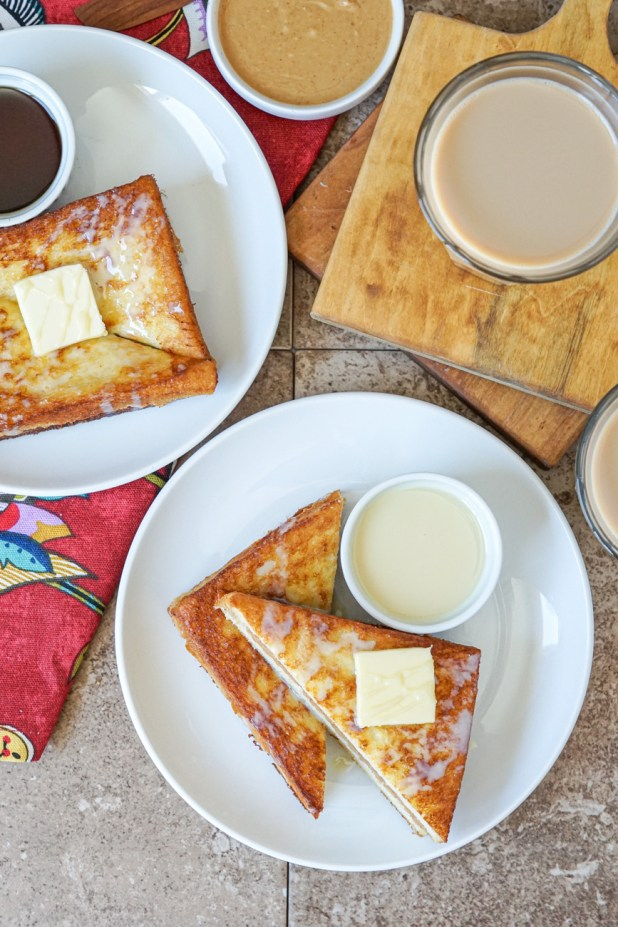 Aerial view of Hong Kong Style French Toast on two white plates alongside peanut butter, maple syrup, sweetened condensed milk, and two glasses of milk tea.