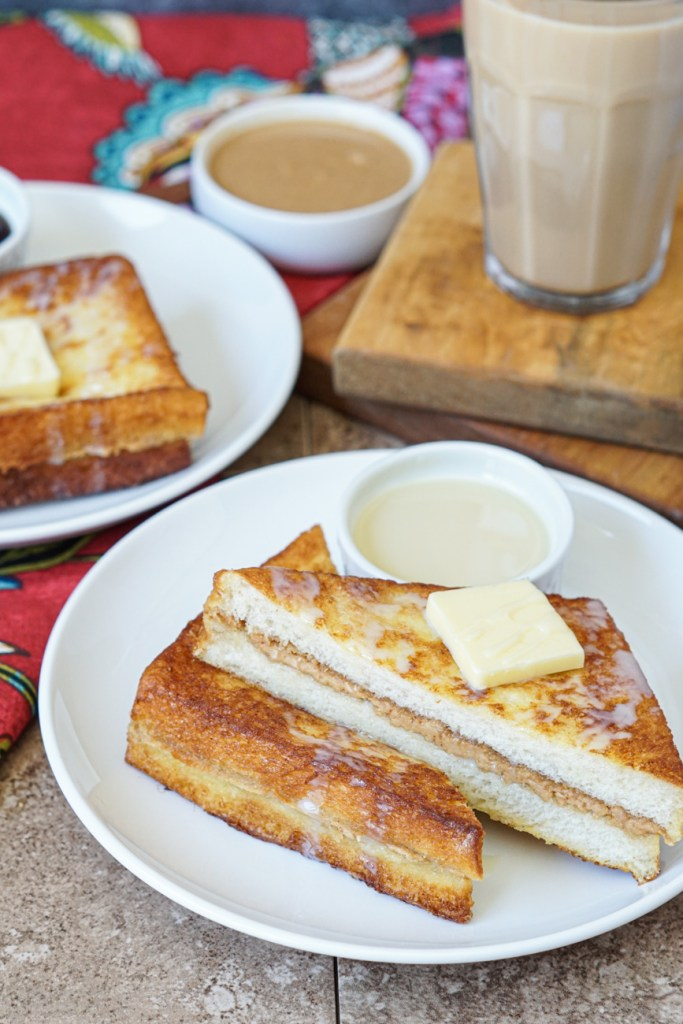 Hong Kong Style French Toast topped with butter and sweetened condensed milk on two white plates with a glass of milk tea on a wooden board and more peanut butter in a white bowl.