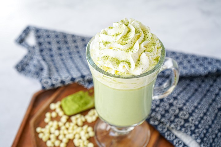 Matcha Hot Chocolate in a tall glass with whipped cream on top.