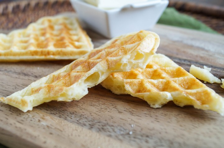 A heart-shaped Waffle Pão de Queijo (Brazilian Cheese Bread Waffles) cut in half to show the cheese center.