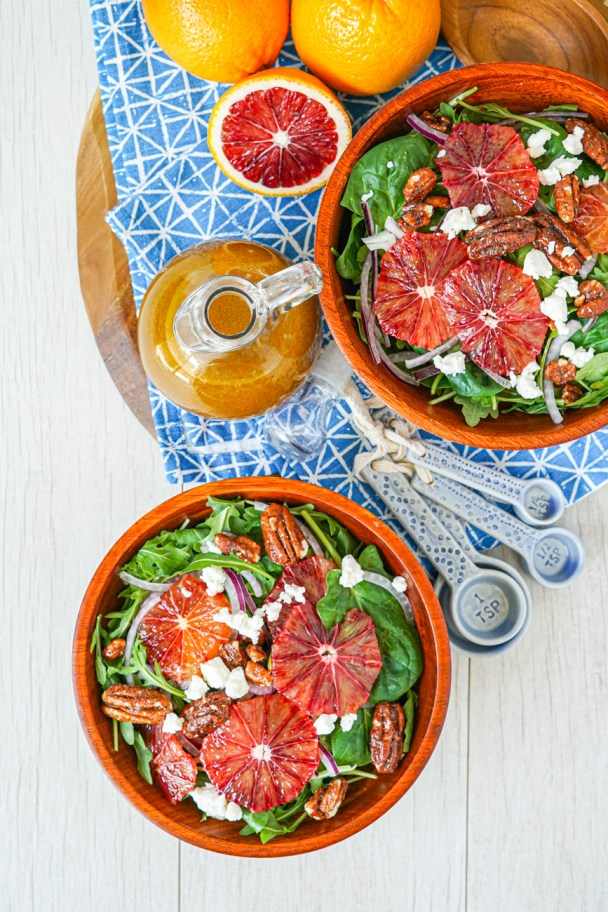 Aerial view of Blood Orange Vinaigrette in a glass jar next to two wooden bowls filled with blood orange salad.