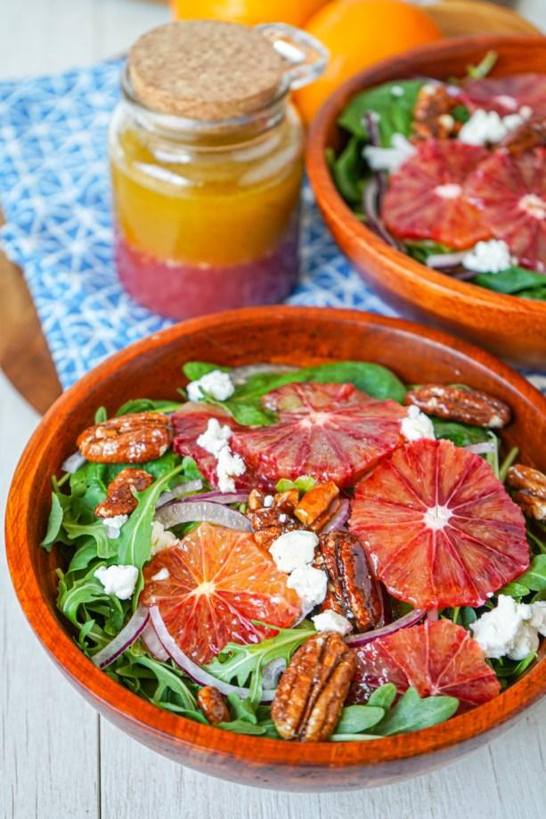 Close up of Blood Orange Salad in a wooden bowl with jar of Blood Orange Vinaigrette in the background.