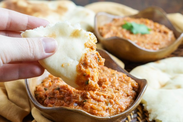 Dipping a piece of naan into Rougaille Pistache (Mauritian Peanut Sauce).