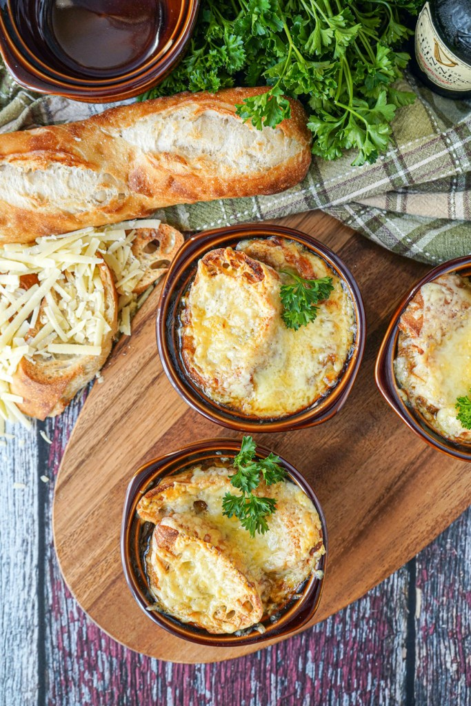 Aerial view of Guinness Onion Soup in three brown bowls topped with cheese and parsley.