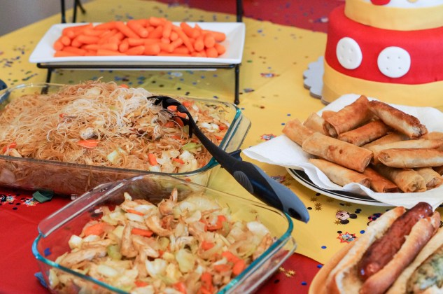 Lumpia, Hot Dogs, Pancit, and Carrots on a table.