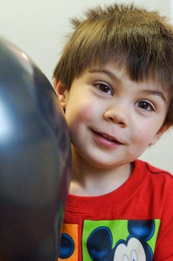 Boy holding a black balloon.