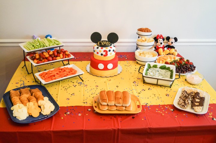 Red and yellow table with food and a Mickey Mouse cake.